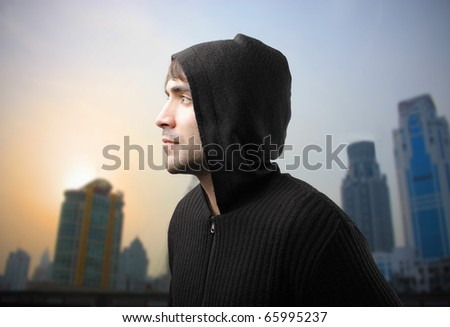 Young man in casual clothes with cityscape on the background - stock photo