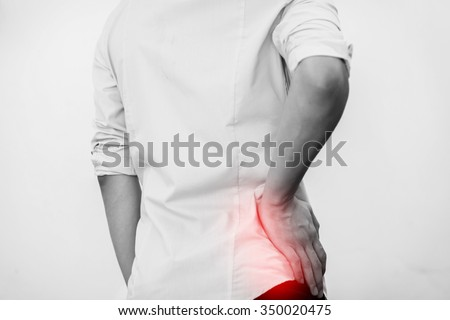 Young man in casual office shirt having hip pain (Selective Focus) - stock photo