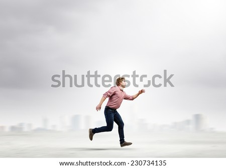 Young man in casual running away from something - stock photo
