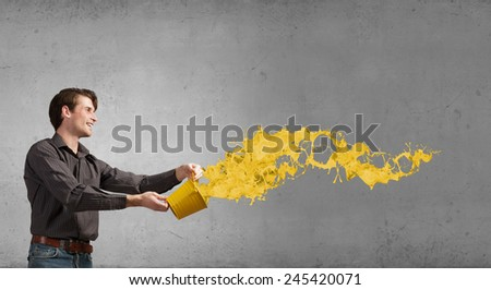 Young man in casual splashing paint from bucket - stock photo