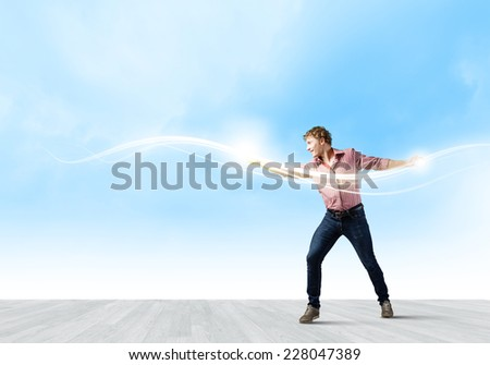 Young man in casual throwing magic light - stock photo