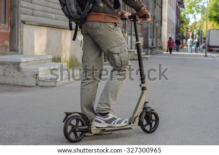 Young man in casual wear on kick scooter on city street