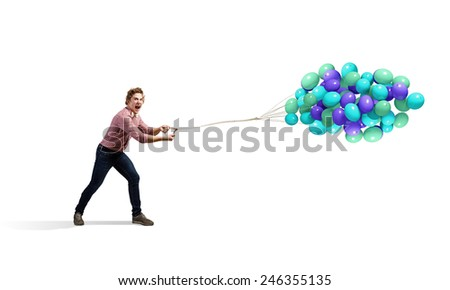 Young man in casual with bunch of colorful balloons - stock photo