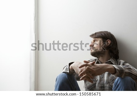 Young man in checked shirt siting with hands clasped against a wall - stock photo