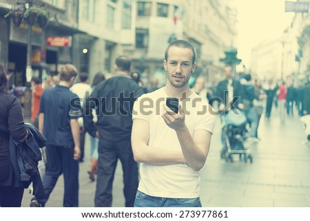 Young Man in city with mobile phone walking, background is blured city street - stock photo