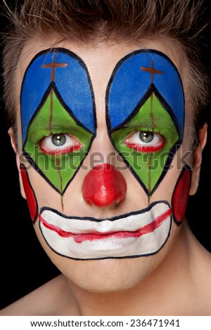 Young man in clown makeup in the studio on a black background - stock photo