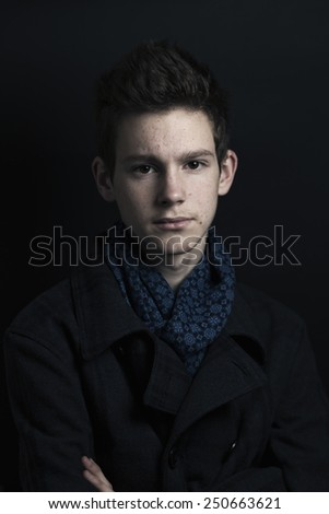 Young man in coat and scarf, portrait - stock photo