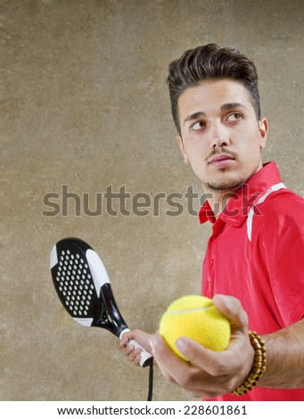 Young man in concrete court ready for paddle tennis serve - stock photo