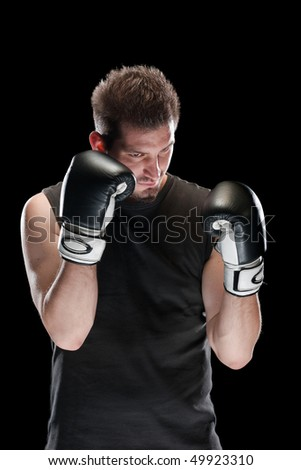 Young man in defensive boxing pose isolated on black - stock photo
