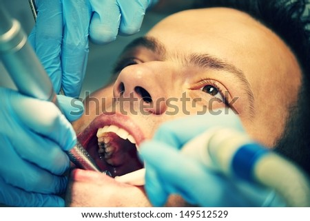 Young man in dentist office - selective focus - stock photo