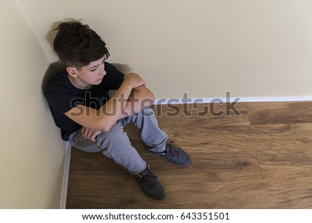 Young man in depression. Isolated on gray background. Sad teenager boy. Sad depressed boy in an empty room. stressed out male teenager. Negative human emotion. Teen depression, pain, suffering.