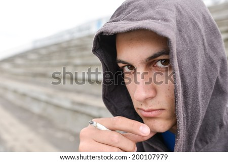 Young man in depression smoking a cigarette on a stadium and looking at the camera - stock photo