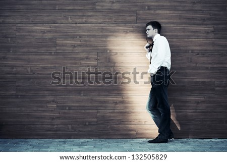 Young man in depression standing against a wall - stock photo