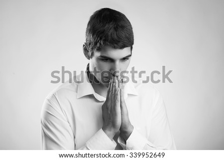 young man in despair praying sorrow - stock photo