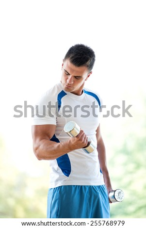 young man in fintess sport club exercise with weights and relaxing - stock photo