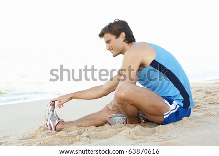 Young Man In Fitness Clothing Stretching On Beach