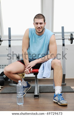young man in fitness sport club exercise with weights and relaxing - stock photo