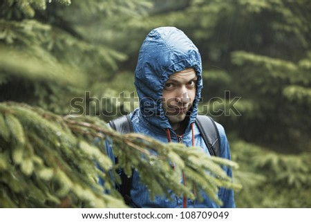 Young man in forest in rain - selective focus - stock photo