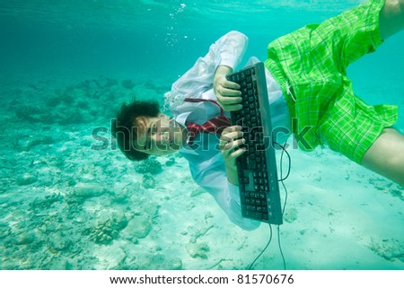 Young man in formal clothes with keyboard working and swimming underwater - stock photo