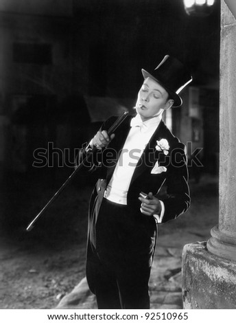 Young man in formal clothing lighting his cigarette with his walking stick - stock photo