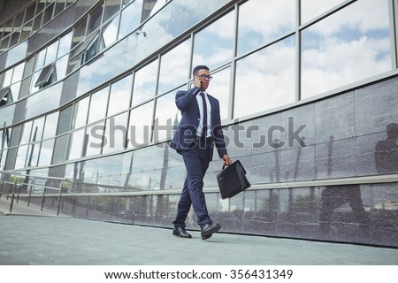 Young man in formalwear walking along modern building during telephone consultation