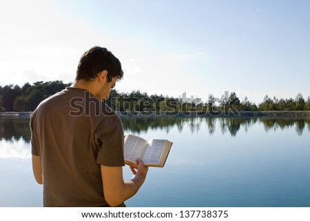 Young man in front of lake reading the Bible (King James Version) - stock photo