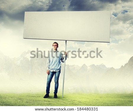 Young man in glasses holding blank banner. Place for text - stock photo