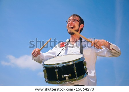 young man in glasses plays on drum - stock photo