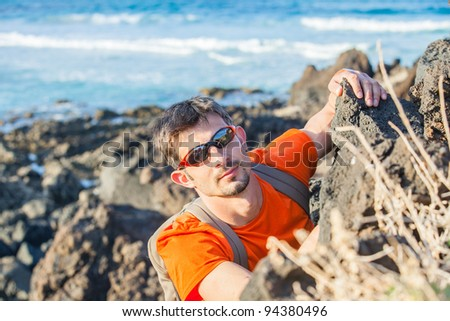 Young man in glasses with backpack climbing indoor wall. Backround sea - stock photo