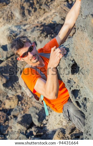 Young man in glasses with backpack climbing indoor wall. Vertical view - stock photo