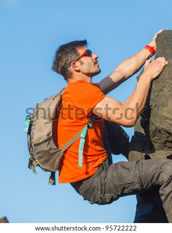 Young man in glasses with backpack climbing outdoor wall. - stock photo