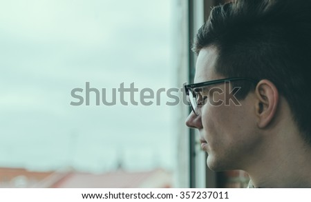 Young man in glasses with closed eyes looking in window - stock photo