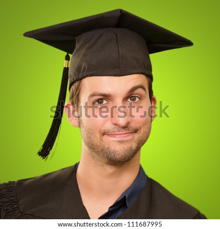 Young Man In Graduation Gown On Green Background - stock photo