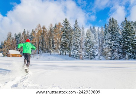Young man in green jacket running in deep snow - stock photo