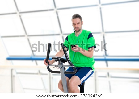 young man in green shirt train with fitness machine and listening music - stock photo