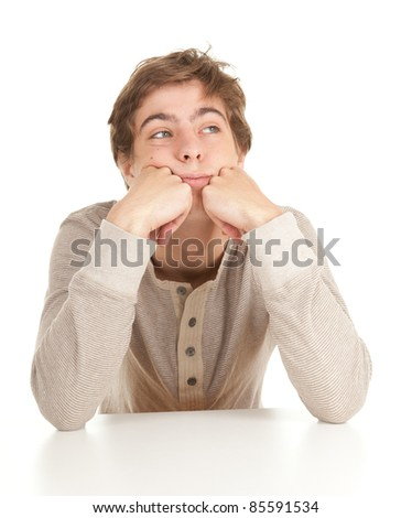 young man in grey slouse leaning on table, white background, series - stock photo
