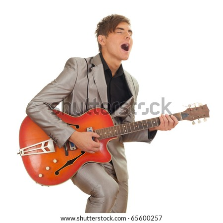 young man in grey suit playing on electric guitar