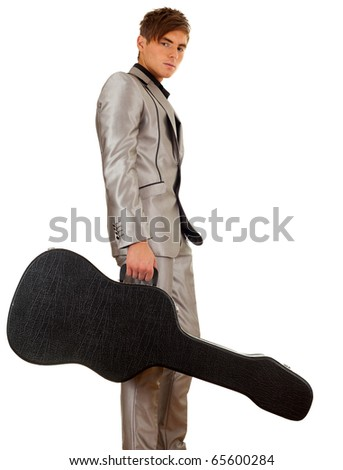 young man in grey suit with black case on guitar - stock photo
