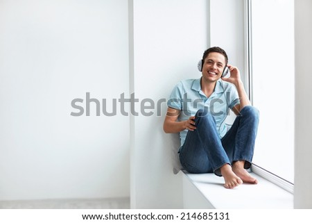 Young man in headphones at home - stock photo