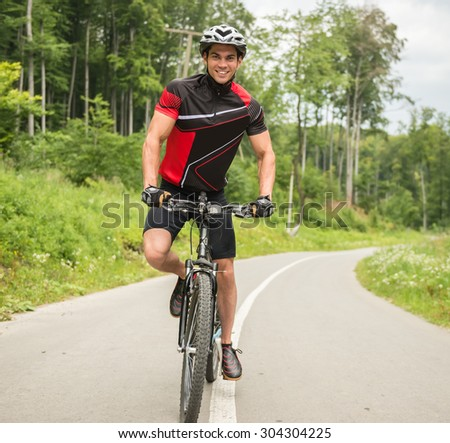 Young man in helmet riding on mountain bicycle on the forest road. - stock photo