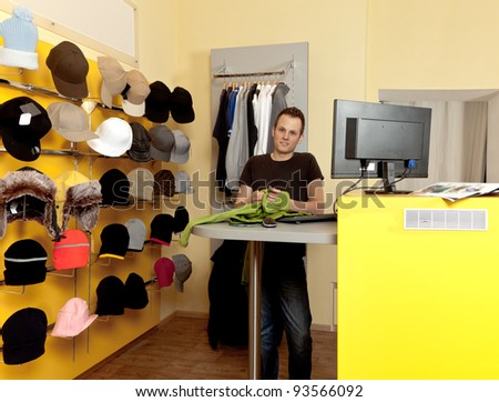 Young Man in her clothing store and smiling - stock photo