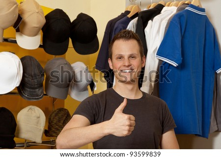 Young Man in her clothing store smiling and showing thumbs up - stock photo