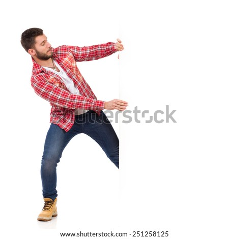 Young man in jeans and lumberjack shirt pulling a big white banner. Full length studio shot isolated on white.