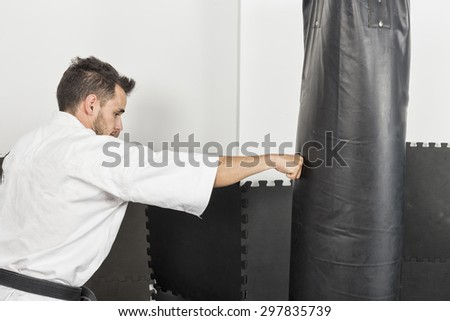 Young man in kimono throwing punches at a heavy punching bag during his training