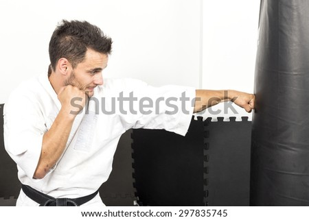 Young man in kimono throwing punches at a heavy punching bag during his training - stock photo