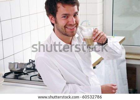 young man in kitchen and drinking coffee
