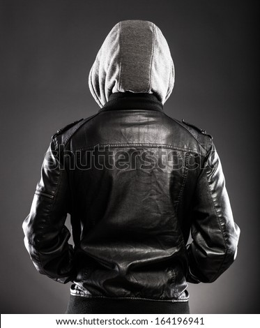 Young man in leather jacket and hood rear view on back - stock photo