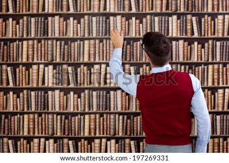 Young man in library take book from shelf - stock photo