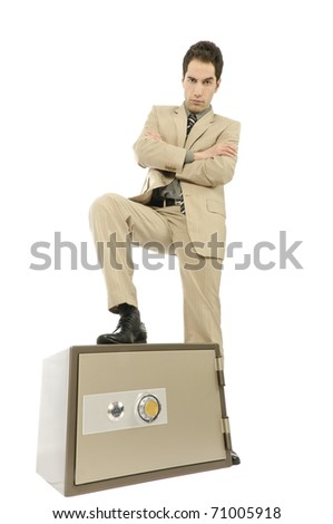 Young man in light suit, the arms folded and with one foot on a safe, isolated on a white background - stock photo