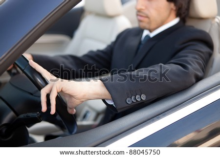 Young man in luxury sports car - stock photo